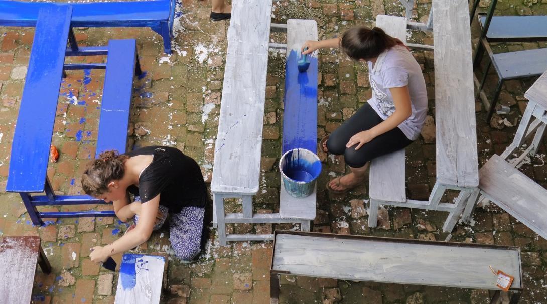 Voluntarias ayudando a personas con VIH en Nepal ayudan a pintar escritorios.